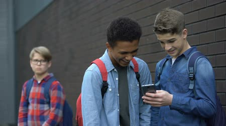 condemn : Two bully boys posting offensive video about upset guy behind, cyberbullying