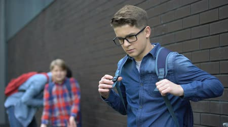 piada : Teenagers mocking boy in eyeglasses, spreading malicious rumors, verbal bullying