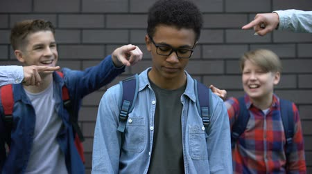 vélemény : Group of cruel teenagers pointing fingers at black boy, humiliation and racism