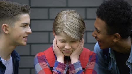 minoria : Spiteful high school students teasing boy, calling names, face-to-face bullying Stock Footage