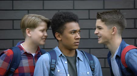 multikulturális : Evil students teasing black boy face-to-face, telling insults, racial bullying