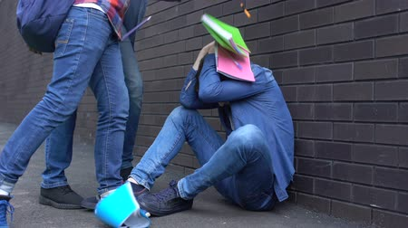 abused : Students throwing things out of backpack on boy head, teenage bullying at school