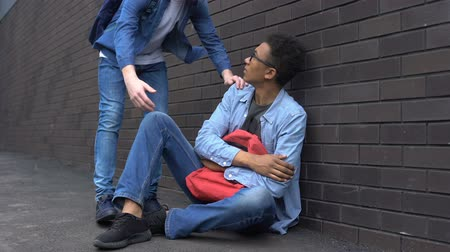 yardım hattı : Teenage student giving helping hand to bullied afro-american boy, stop racism