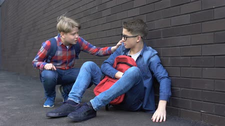 телефон доверия : Kind teenage boy starting friendship with bullied student, helpline for children Стоковые видеозаписи