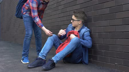 одноклассник : Kind teenage student giving helping hand to bullied nerd boy, supportive friend Стоковые видеозаписи