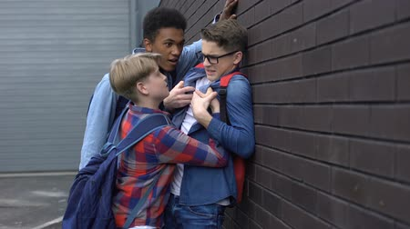 cruelty : Cruel teenage students bullying nerd boy in school backyard, social problem, conceptual
