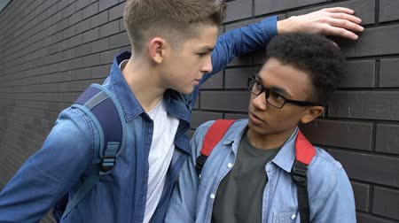 nerd : Impudent teenager taking away glasses from insecure black boy, mocking bad sight