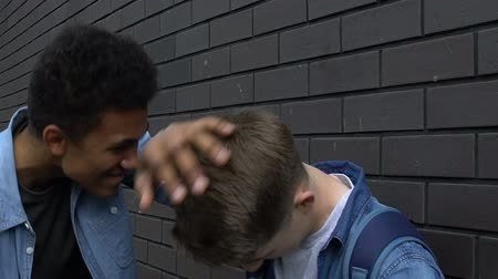 abused : Afro-american guy giving caucasian classmate slap upside the head, humiliation
