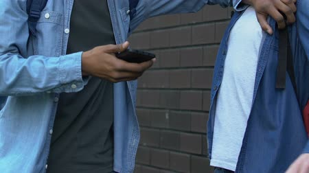 schoolyard : Rude black teenager grabbing caucasian boys smartphone trying to show disrespect Stock Footage