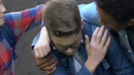 dishonor : Aggressive multietnic teens humiliating caucasian boy in glasses violence victim