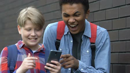 dishonor : Disrespectful multiracial guys scrolling smartphone and laughing, mocking