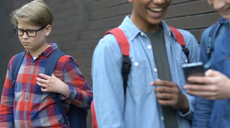 dishonor : Multiracial teens scrolling smartphone and mocking classmate, bullying online