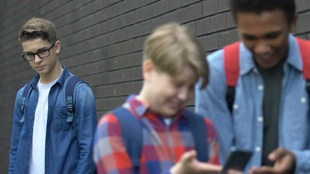 schoolyard : Cruel multiethnic students scrolling phone and mocking nerd classmate online