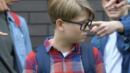 хулиган : Group of students pointing fingers at boy in eyeglasses, outsider humiliation