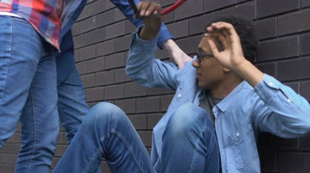 outsider : Multiracial students humiliating afro-american guy in eyeglasses, discrimination Stock Footage