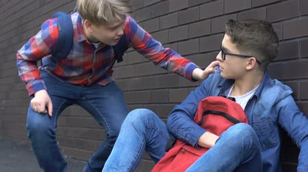 abused : Openhearted schoolboy comforting bullying victim in schoolyard, social problem Stock Footage