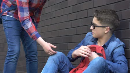 schoolyard : Teenage student giving hand to classmate, supporting humiliated abuse victim Stock Footage