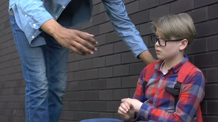 schoolyard : African-american teenager proposing hand to support humiliated bullying victim