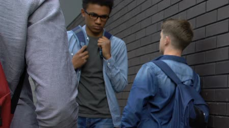 médio : European students aggressively looking at afro-american guy, discrimination Stock Footage