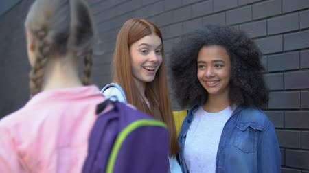 social inequality : Female teenagers laughing at new student passing by, school rejection, offend