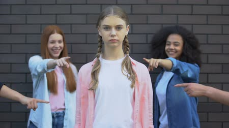 condemnation : Female students pointing fingers at teenager, school rejection, insecurities Stock Footage