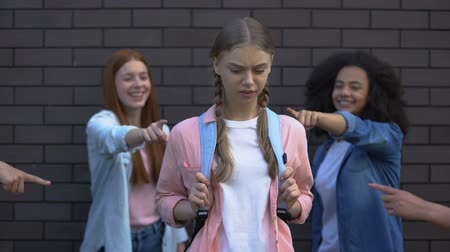 social inequality : Female peers pointing fingers desperate schoolgirl, college teasing condemnation Stock Footage