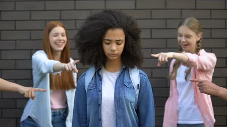 spolužák : Cruel group of teens pointing fingers at curly afro-american schoolgirl, racism