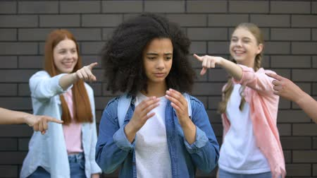 social inequality : Humiliated black schoolgirl covering face hands, college peers pointing fingers Stock Footage