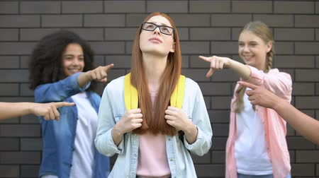 desperate student : Red-haired schoolgirl suffering bullying, students pointing fingers, conflict