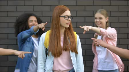 social inequality : Teenagers pointing fingers teasing new smart classmate in eyeglasses school bag Stock Footage