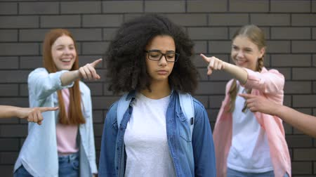 smutek : Mocking classmates pointing fingers at black female teenager in eyeglasses