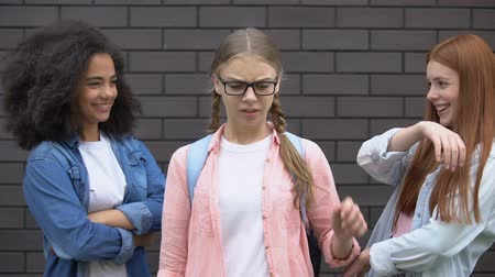 bescheiden : Teenagers making fun at modest classmate in eyeglasses, appearance bullying Stockvideo