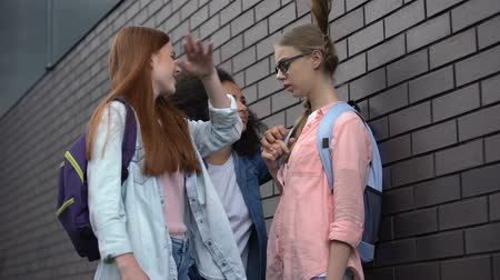 condemnation : Cruel teenagers pushing with elbow shy classmate in eyeglasses school backyard Stock Footage