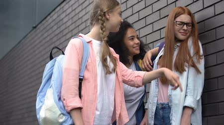 condemnation : Female students pushing with elbow scared schoolgirl, college bullying backyard Stock Footage