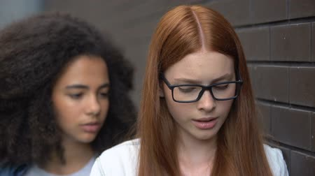 bully : Depressed red-haired teenager eyeglasses suffering insulting classmate, conflict