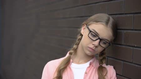 desperate student : Desperate caucasian female teen leaning wall, social rejection, loneliness