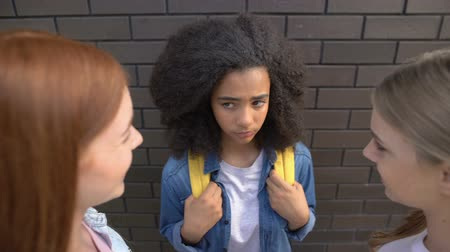 жестокий : Female teenagers looking at younger black schoolmate, bullying problem, abuse