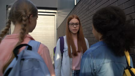 stopping : Confused red-haired teenager in eyeglasses passing by cruel classmates, conflict Stock Footage