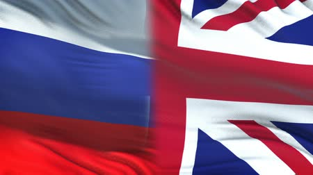 spying : Russia and GB officials exchanging confidential envelope, flags background Stock Footage