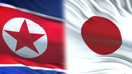 confidentialité : North Korea and Japan officials exchanging confidential envelope, against flags