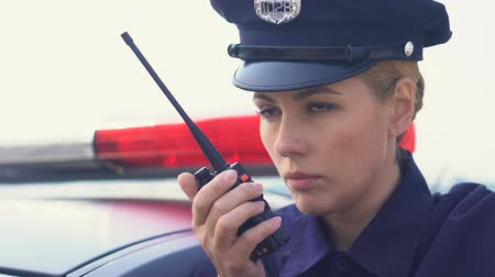 autoradio : Serious police lady accepting call and getting into patrol car, ready for action