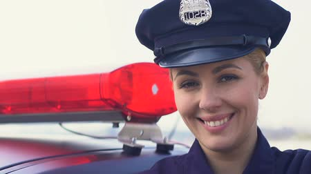 readiness : Lady police officer in cap standing near patrol car and smiling, law protection