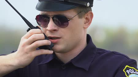 patrolman : Determined police officer communicating on walkie-talkie, exchanging information Stock Footage