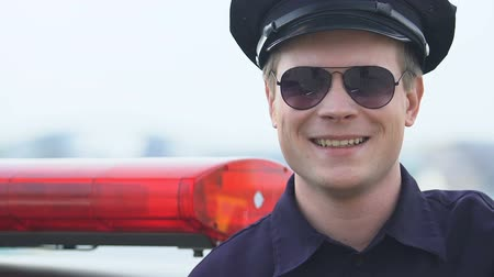 patrolman : Friendly male police officer looking to camera, trusting police, protection