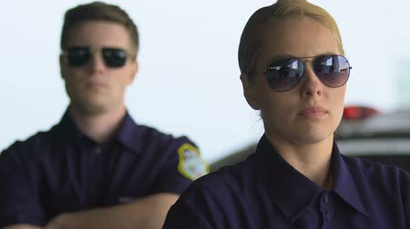patrolman : Determined male and female police officers in eyeglasses looking to camera, team