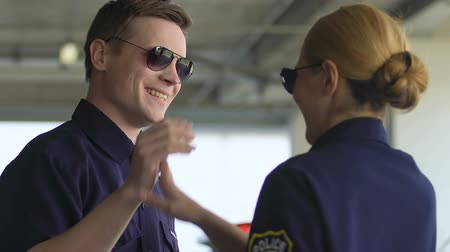 patrolman : Male and female patrol officers giving high-five and going to squad car, team Stock Footage