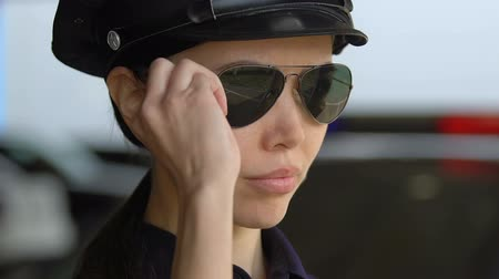 first officer : Young female police academy student in cap putting on sunglasses, first duty