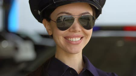 helpful : Friendly asian patrol lady in cap and sunglasses smiling to camera, protection