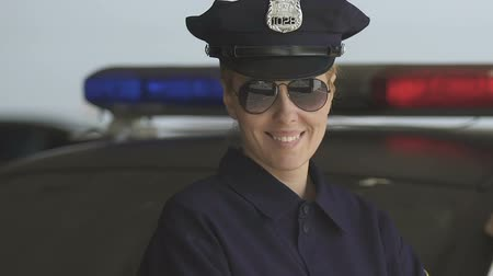 behulpzaam : Friendly patrol woman in hat and sunglasses smiling to camera, law protection