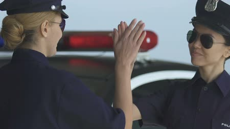 squad car : Police lady making high-five gesture trustful relations in squad gender equality